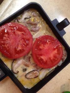 冷蔵庫にあった、トマトと シイタケ、豚バラ肉にタマネギ、ニンニク、玉子、牛乳で作った朝食。 トマト以外は軽く炒め、一度ホットサンドメーカーを火からはずし、そこに玉子と牛乳を。で、よくかき混ぜたところに、塩コショウ、オレガノを振り、トマトを置く。 中弱火で、約三分。 片面だけを弱火でじっくり焼いたら、できあがり。 こうすれば、調理道具はホットサンドメーカーだけですむ。洗い物も少なくていい。 怠け者が作る『のらくらオムレツ』である。