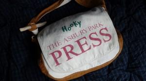 最近よく使っているのは、輸入雑貨屋で買ったニューズペーパーバッグ。新聞配達少年が肩から下げて走り回っていた時代のバッグだ。ショルダーひもに流木を結びつけ、長さ調節をしている。