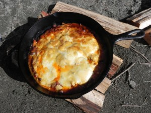 まずは、「TOMOの満月焚き火グラタン」。ことこと煮込んだミートソースをベースに、茄子とズッキーニ、キノコ、チーズなどなどをLODGE 10 1/4 スキレットへ載せ、ストーブの中へ。