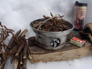 焚き火台となる土台に紙くずやたきつけをおき、その上にケリーケトルを置く